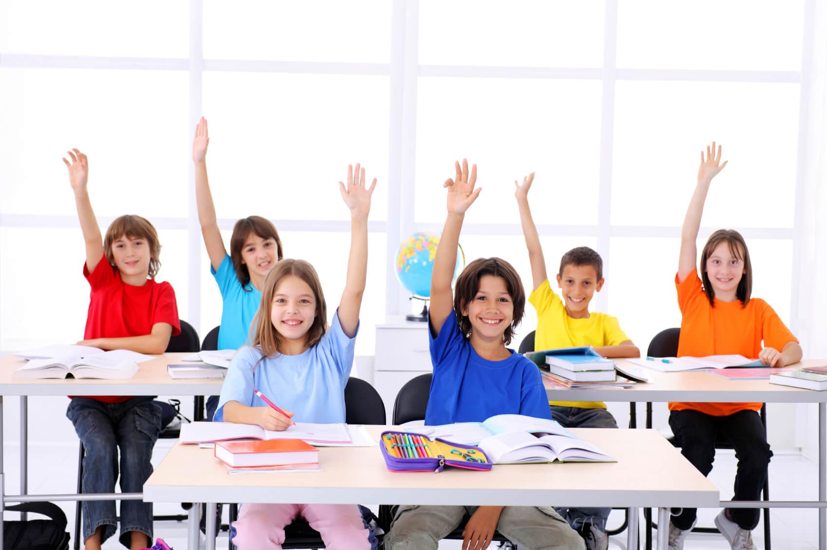 Cute school students raising hands in a modern classroom.
