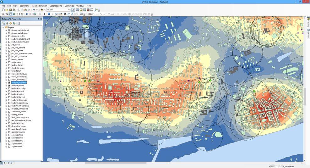 Rys.3. Ostateczny wynik analizy – tylko nośniki reklamowe oznaczone kolorem zielonym spełniły dwa dodatkowe kryteria, gdyż jednocześnie znajdowały się w obszarze o gęstości zaludnienia powyżej 12,5 tys. os./km2 (żółte i pomarańczowe warstwice), a zarazem nie były oddalone o więcej niż 200 m od przynajmniej jednego budynku skupiającego wybraną grupę docelową (czarne granice buforów).