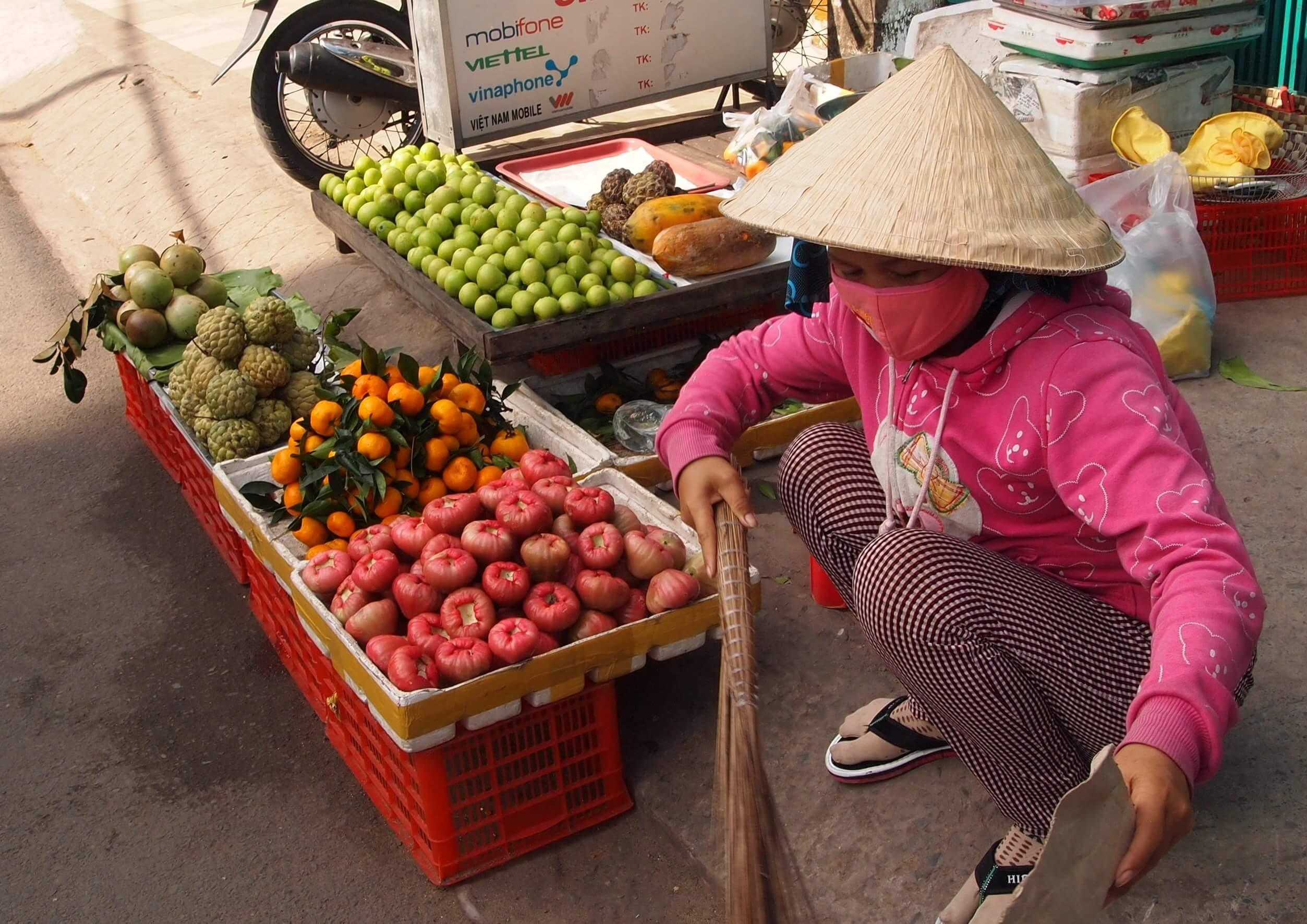 Kobieta sprzedająca owoce na targu przy ulicy