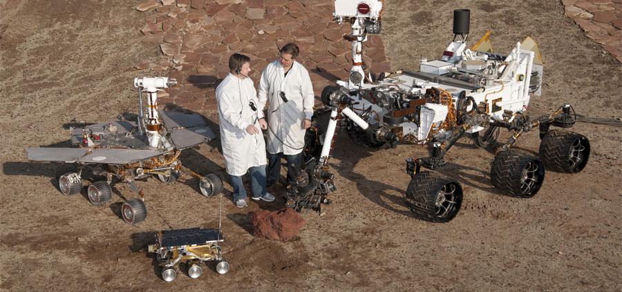 Rys 1. Istnieje wiele różnych modeli łazików marsjańskich dostosowanych do różnych warunków terenowych i charakteryzujących się najlepszą stabilnością. W lewym dolnym rogu poniższego zdjęcia przedstawiono Sojourner, który działał w 1997 roku. Za nim widać łazik Opportunity, który pozostaje aktywny od 2004 roku. Na podstawie tego samego projektu wykonano łazik Spirit. Curiosity, łazik aktywny od 2012 roku, jest widoczny po prawej stronie zdjęcia.