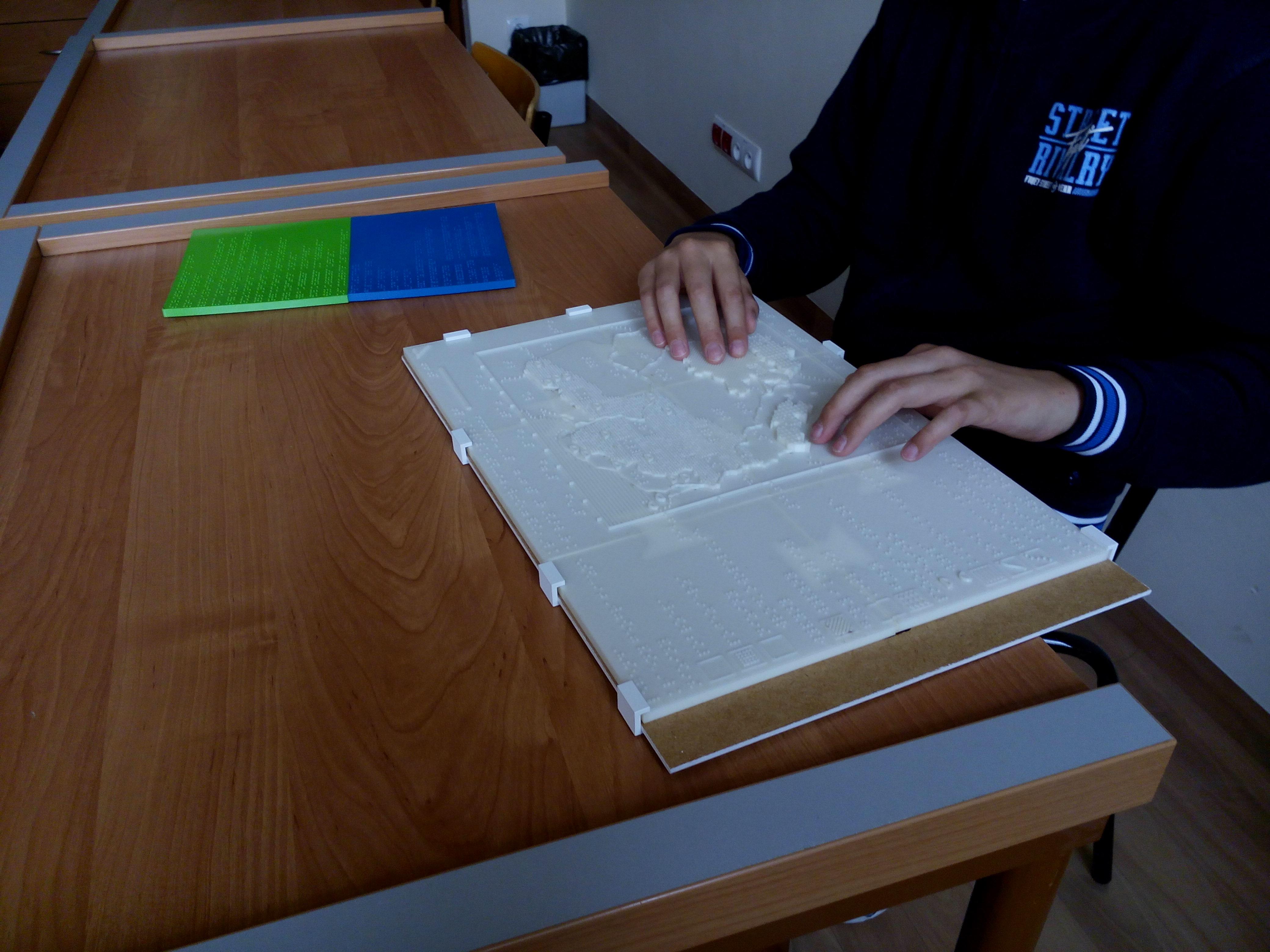 Rys. 4. Uczeń niewidomy w trakcie testów z opracowanym arkuszem mapy dotykowej, źródło: opracowanie własne.