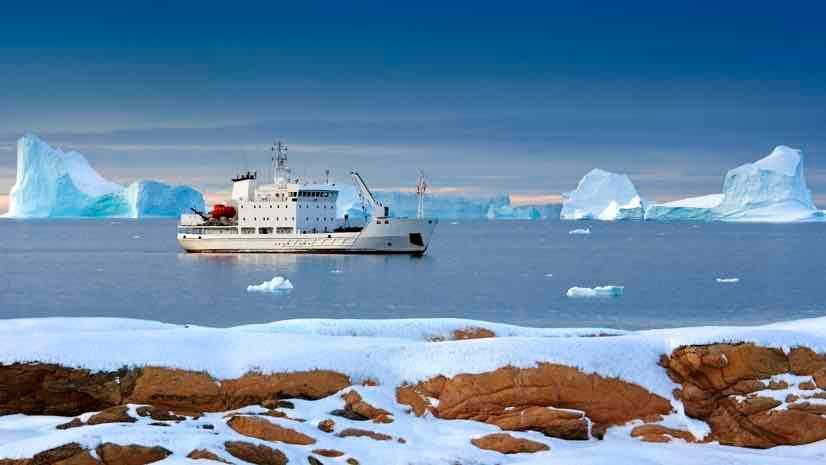 Rys. 1. Turystyczny lodołamacz na wodach Arktyki u wybrzeży Grenlandii. W tle widać góry lodowe.